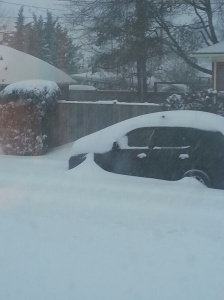The car across the street, with the wind blowing the snow AWAY from it!